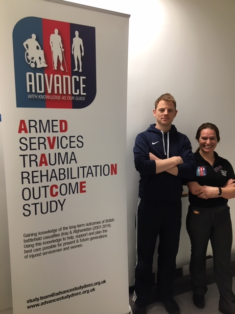 ADVANCE participant Jonathan Grave and staff member Mel Kaya-Barge standing next to an ADVANCE banner